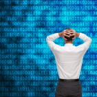 Composite image of businessman standing back to camera hands on head staring at blue binary code