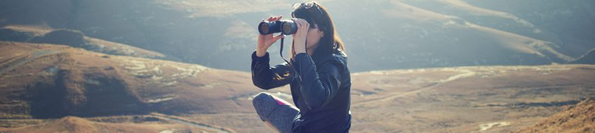 On a windswept hill a squatting woman peers through binoculars.