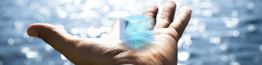 Against the backdrop of a sparkling lake, an outstretched palm holds a blue, virtual cube.