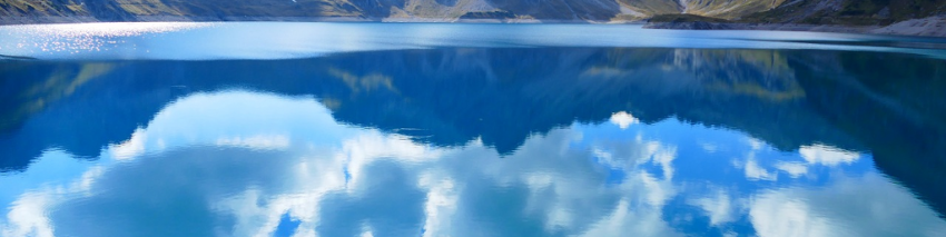 Mountains and a bright, cloudy sky reflected in a clear lake