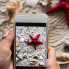 In front of a red sea star and shells on a beach hands hold a smart phone that has a picture of the scene on its screen