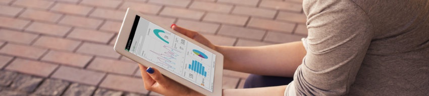 Against the background of a brick patio, a seated woman holds a white tablet displaying a Power BI dashboard