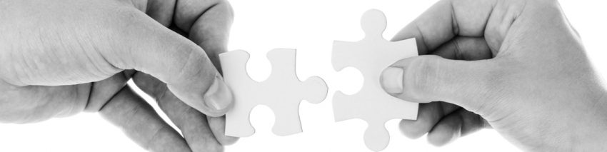Black and white photo of two hands fitting two puzzle pieces together